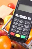 Payment terminal with fresh fruits and vegetables, cashless paying for shopping, finance concept. Payment terminal, credit card reader, fresh fruits and Royalty Free Stock Photo