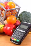Payment terminal with fresh fruits and vegetables, cashless paying for shopping. Payment terminal, credit card reader and fresh fruits with vegetables, cashless Stock Photography