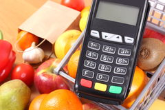 Payment terminal with fruits and vegetables, cashless paying for shopping, finance concept. Payment terminal, credit card reader and fresh fruits and vegetables Stock Photography