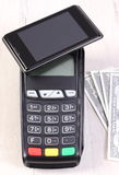 Payment terminal with mobile phone with NFC technology and currencies dollar, cashless paying for shopping or products Royalty Free Stock Images