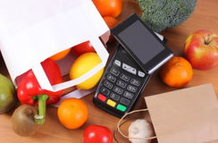 Payment terminal and mobile phone with NFC technology, fruits and vegetables, cashless paying for shopping concept. Credit card reader, payment terminal with Stock Photography