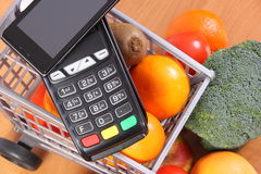 Payment terminal and mobile phone with NFC technology, fruits and vegetables, cashless paying for shopping. Payment terminal, credit card reader with mobile Stock Photo