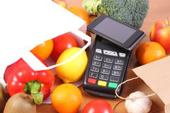 Payment terminal and mobile phone with NFC technology, fruits and vegetables, cashless paying for shopping. Credit card reader, payment terminal with mobile Royalty Free Stock Images