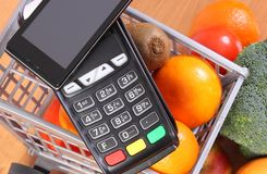 Payment terminal and mobile phone with NFC technology, fruits and vegetables, cashless paying for shopping. Payment terminal, credit card reader with mobile Royalty Free Stock Photo