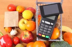 Payment terminal and mobile phone with NFC technology, fruits and vegetables, cashless paying for shopping. Payment terminal, credit card reader with mobile Stock Photos
