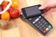Payment terminal and mobile phone with NFC technology, fruits and vegetables, cashless paying for shopping. Using credit card reader, payment terminal with Stock Images