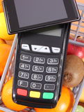 Payment terminal and mobile phone with NFC technology, fruits and vegetables, concept of cashless paying for shopping. Payment terminal, credit card reader with Royalty Free Stock Photos
