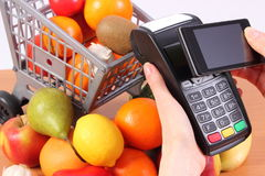 Payment terminal and mobile phone with NFC technology, fruits and vegetables, concept of cashless paying for shopping. Using credit card reader, payment terminal Stock Photos