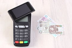 Payment terminal with mobile phone with NFC technology and polish currency, cashless paying for shopping or products. Payment terminal with mobile phone with NFC Stock Photo