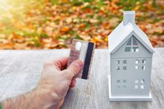 Payment of utilities concept. plastic card in hand of man and model of mini house. Payments for the house. Costs house. Stock Photos