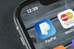 PayPal在苹果计算机iPhone x智能手机屏幕特写镜头的应用象 PayPal app象 PayPal是网上电子财务 库存照片