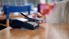 Paypass begrepp Kvinnan gör en betalning genom att använda smartphonen 4K lager videofilmer