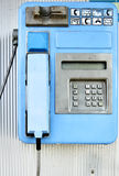 Payphone. Blue public telephone close-up on the wall stock images