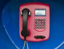 Payphone on blue background. phone with braille table buttons.  stock photos