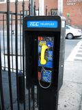 Payphone. Local payphone near a fence on a local street in Queens New York stock photo