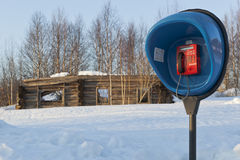 Payphone op het achtergrond geruïneerde blokhuis in de wildernis Rus Stock Afbeeldingen