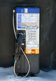 Payphone in Winter. Partially snow-covered stock photo