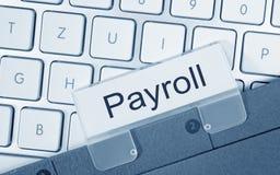 Payroll folder on computer keyboard