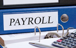 Payroll. Text 'payroll' in uppercase black letters on blue binder with pen and electronic calculator placed alongside Royalty Free Stock Photos
