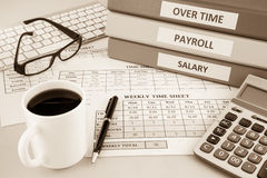 Payroll time sheet for human resources, sepia tone. Human resources documents: payroll, salary and employee  time sheets place on office table with cup of coffee Royalty Free Stock Image
