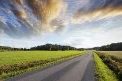 Pays-route sous des nuages de coucher du soleil Image stock