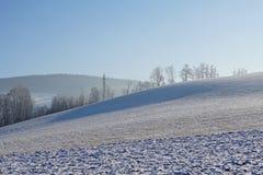 Paysage accidenté en hiver avec un principal courant électrique élevé de pylône grand de l'électricité à l'arrière-plan Photos libres de droits