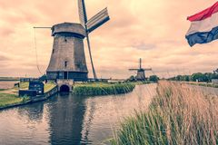 Paysage avec deux moulins à vent et drapeau néerlandais Oterleek Hollandes Hollande images stock