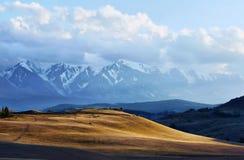 Paysage avec la vallée ensoleillée et les montagnes neigeuses Image libre de droits