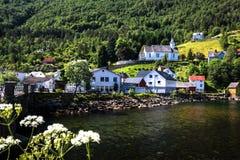 Paysage avec la vue d'un village norvégien au milieu des montagnes par le fjord de Geiranger en été image libre de droits