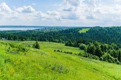 Paysage avec le champ, la forêt et les collines images stock
