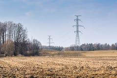 Paysage avec les lignes électriques à haute tension de soutiens et champ labouré en premier ressort photos libres de droits