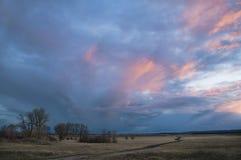 Paysage avec les nuages colorés avant coucher du soleil Photographie stock libre de droits