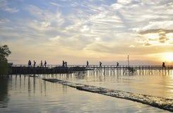 Paysage blanc noir de plage de coucher du soleil derrière le pont images libres de droits
