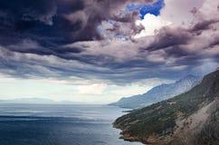 Paysage côtier Bord de la mer avec les montagnes rocheuses contre le contexte du ciel pluvieux dramatique photographie stock libre de droits