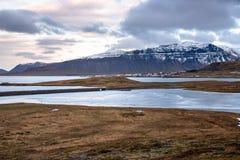Paysage côtier en Islande avec un village de bord de la mer au pied d'une montagne majestueuse photo libre de droits
