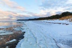 Paysage côtier d'hiver avec de la glace et la neige sur la plage Photographie stock libre de droits