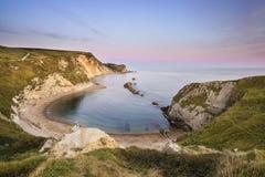 Paysage côtier de crique naturelle renversante au coucher du soleil avec beau Photographie stock
