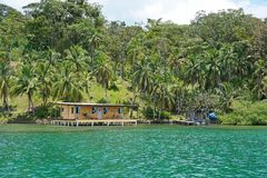 Paysage côtier luxuriant avec la maison au-dessus de l'eau Photographie stock