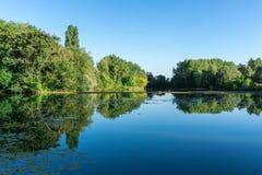 Paysage calme avec des arbres, se reflétant dans l'eau photographie stock