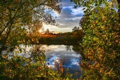 Paysage coloré d'automne un jour ensoleillé avec des arbres avec l'eau et des nuages Photo stock