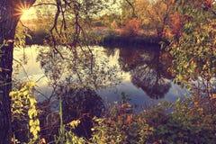 Paysage coloré d'automne un jour ensoleillé avec des arbres avec l'eau et des nuages Images libres de droits