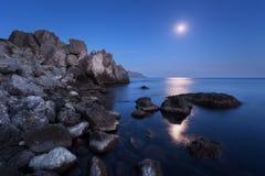 Paysage coloré de nuit avec la pleine lune, le chemin lunaire et les roches en été Paysage de montagne à la mer Photo stock