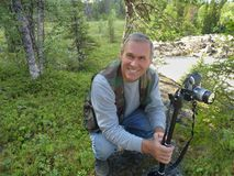 Paysage d'ÉTÉ L'homme avec l'appareil-photo dans la forêt prend des photos Tourisme actif dans la réserve naturelle Photo stock
