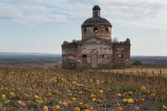 Paysage d'automne avec les potirons et l'église Photographie stock