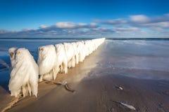 Paysage d'hiver à la mer Ligne en bois gelée de brise-lames à la mer baltique image stock
