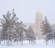 Paysage d'hiver avec l'église de ville Photographie stock
