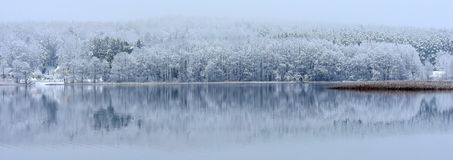 Paysage d'hiver avec la réflexion dans l'eau Lac en Lithuanie Photo stock