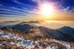 Paysage d'hiver avec le coucher du soleil et brumeux en montagnes de Deogyusan Photos libres de droits