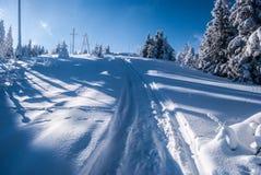 Paysage d'hiver avec les arbres, la neige, le sentier de randonnée et les tours de puissance congelés près de la colline de Wielk Image stock