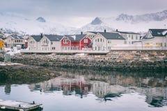 Paysage d'hiver avec les maisons blanches et rouges, réflexion dans l'eau et crêtes de montagne neigeuses, Kabelvag, îles de Lofo image stock